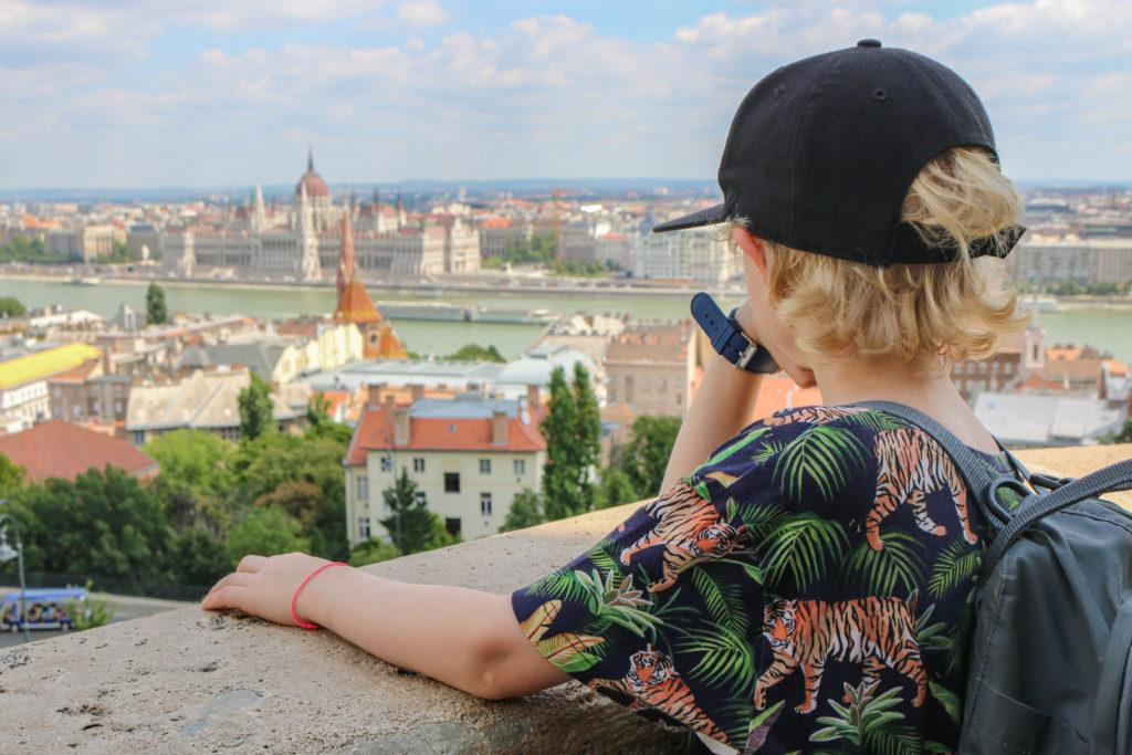 Ein Kind schaut auf die Donau mit dem Budapester Parlament.